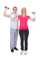 Portrait Of Couple Exercising With Dumbbells