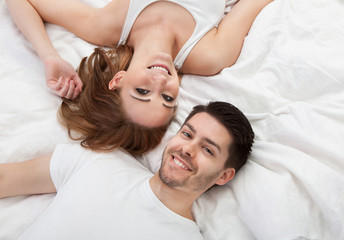 Portrait of happy young couple lying on bed