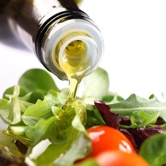 Close-up of olive oil pouring on salad.