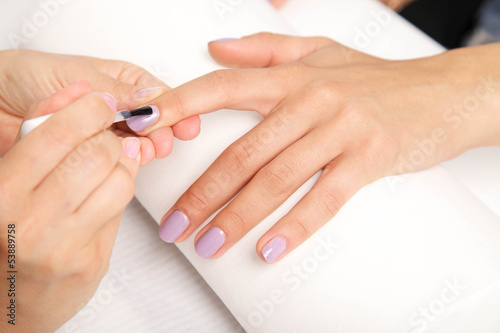Manicure - Beautiful manicured woman's nails with violet nail po
