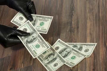 Human hands in black gloves holding dollars