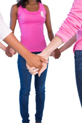 Women wearing pink and ribbons for breast cancer holding hands