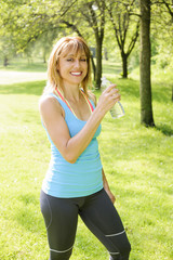 Active woman holding water bottle outside