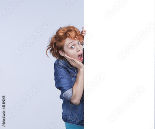 Attractive surprised girl with poster