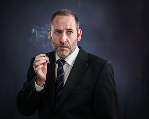 Mature businessman smoking a cigarette