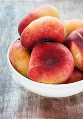Donut peaches in bowl over wooden background