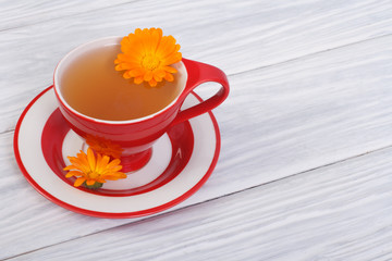 herbal tea with calendula flowers in a red cup