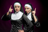 Attractive young nuns posing indoors