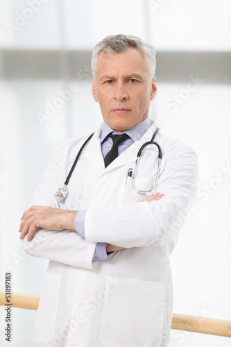 Confident healthcare professional. Confident mature doctor stand