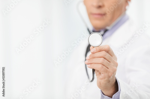 Doctor with stethoscope. Cropped image of mature doctor holding