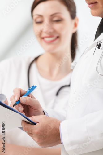 Going through a report. Close-up of two medical doctors writing
