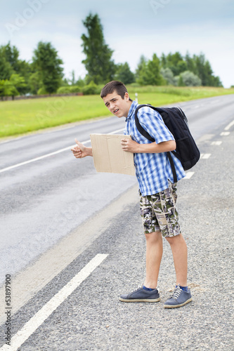 Boy hitchhiker on the road waiting for car to stop in summer