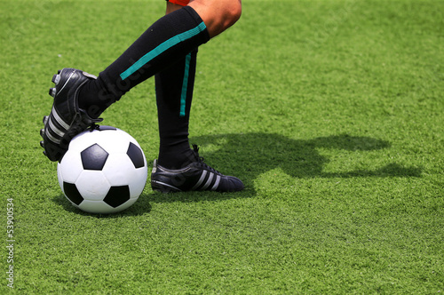 soccer ball with foot of player touching it with adumbration