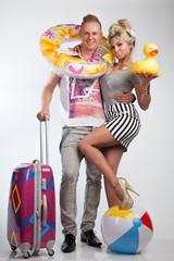 Pärchen mit Koffer und Urlaubsutensilien