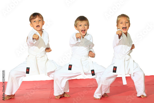 Fototapeta Three children in kimono hit a punch on a white background