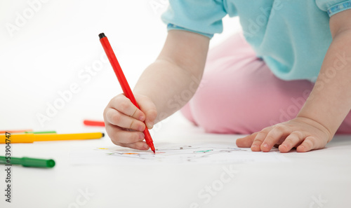 Baby girl drawing with colorful pencils
