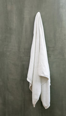 Hanging White Towel draped on Exposed Concrete Wall