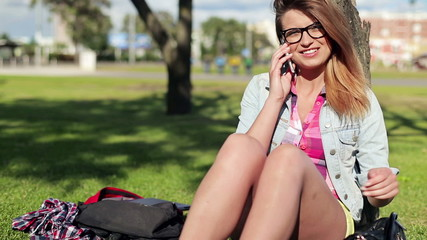 Pretty female student talking on cellphone in the park