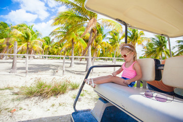 little cute girl sitting in a golf car in a tropical grove