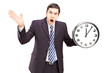 Angry man in a suit holding a clock and gesturing