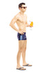 Full length portrait of a guy in swimming shorts holding a cockt