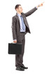 Young businessman with briefcase pointing in a direction
