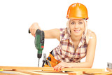Female carpenter with helmet at work using hand drilling machine