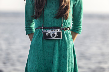 brunette girl with retro camera by the sea