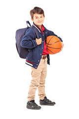 Full length portrait of a schoolboy with backpack holding a bask