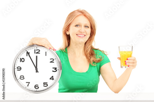Mature woman holding a wall clock and glass of orange juice on a