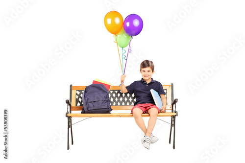 Schoolboy sitting on a wooden bench with books and holding a bun