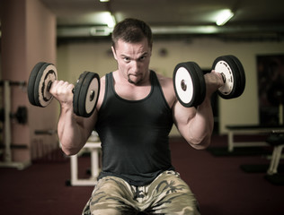 Bodybuilder is doing heavy weight biceps excercise