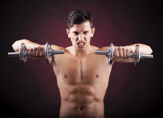 Muscular young man lifting weights on dark background