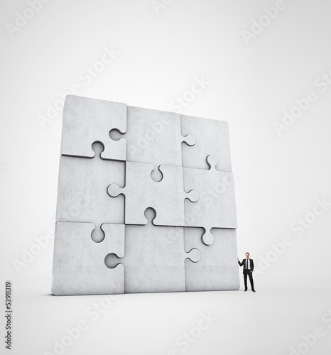 businessman near concrete jigsaw puzzle