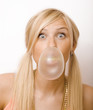 cute blond girl having fun with gum bubbles
