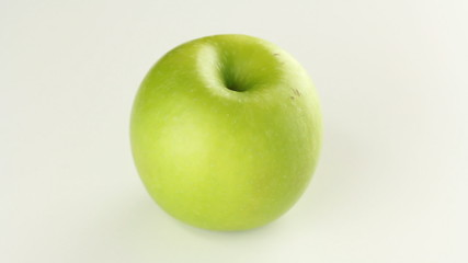 Fresh green apple. Rotating in studio light on white background.
