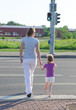 Mother and child crossing the road. Back view.