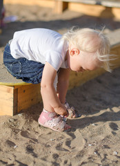 Toddler put on her shoes near sandbox