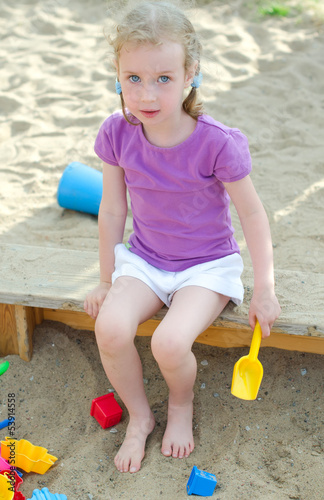 Little girl sitting near sandbox