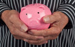 Closeup of a piggy bank in a senior man's hands