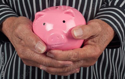 Closeup of a piggy bank in a senior man's hands