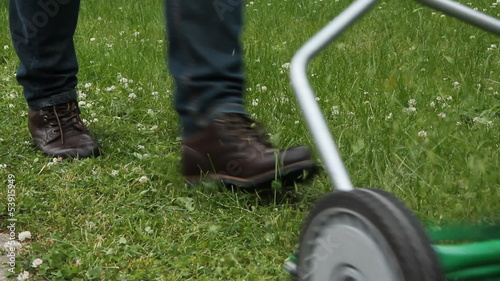 Cutting grass with a push mower.