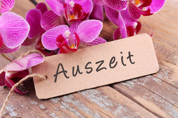 Auszeit - Orchideenblüten und Papierschild auf Holz