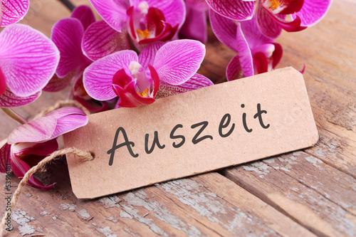 canvas print picture Auszeit - Orchideenblüten und Papierschild auf Holz