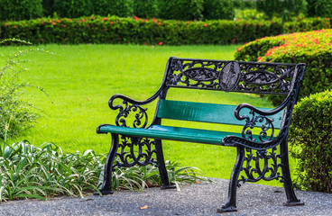 Green Bench in the Park with Green Lawn Background
