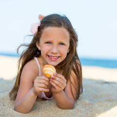 Sweet girl holding seashell on beach.