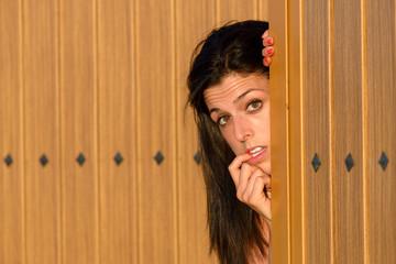 Afraid woman opening house gate