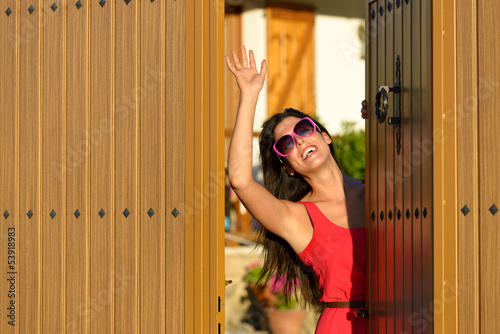 Happy woman opening door and welcoming