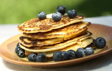 Stack of pancakes with blueberries on garden table