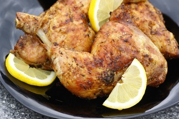 Grilled chicken meat with lemon on black plate